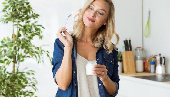 Beautiful young woman eating yogurt at home.