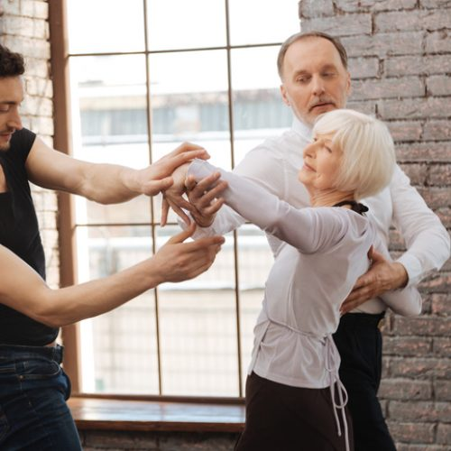 Talented dance instructor teaching aging couple at the ballroom