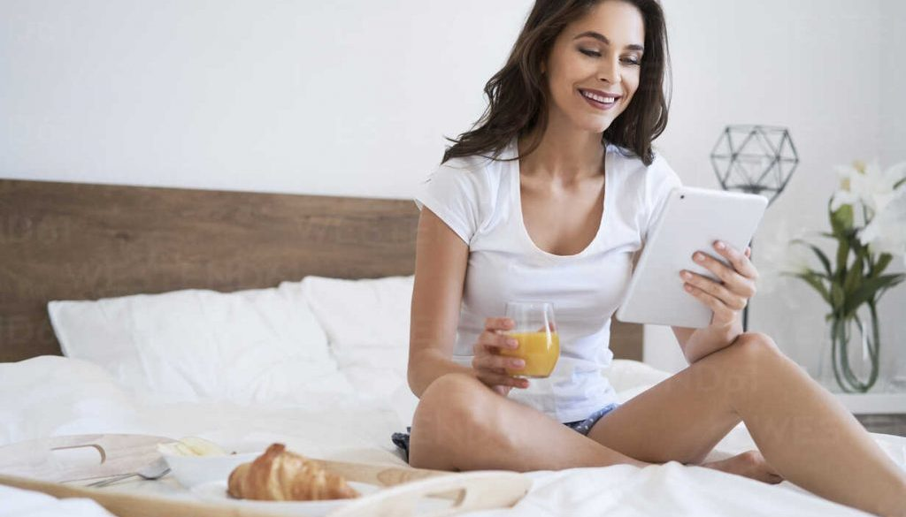 Young woman having breakfast in bed, using digital tablet, reading